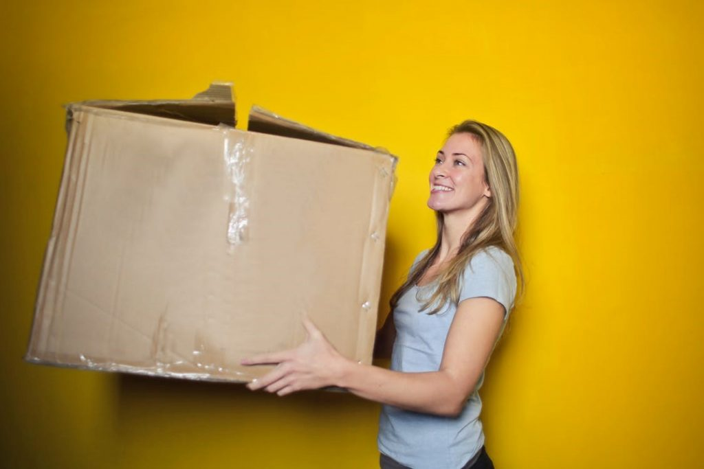 Lady smiling holding a large packaging box set with a yellow background