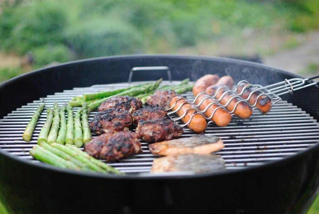 Round BBQ with sizzling asparagus, burgers and sausages