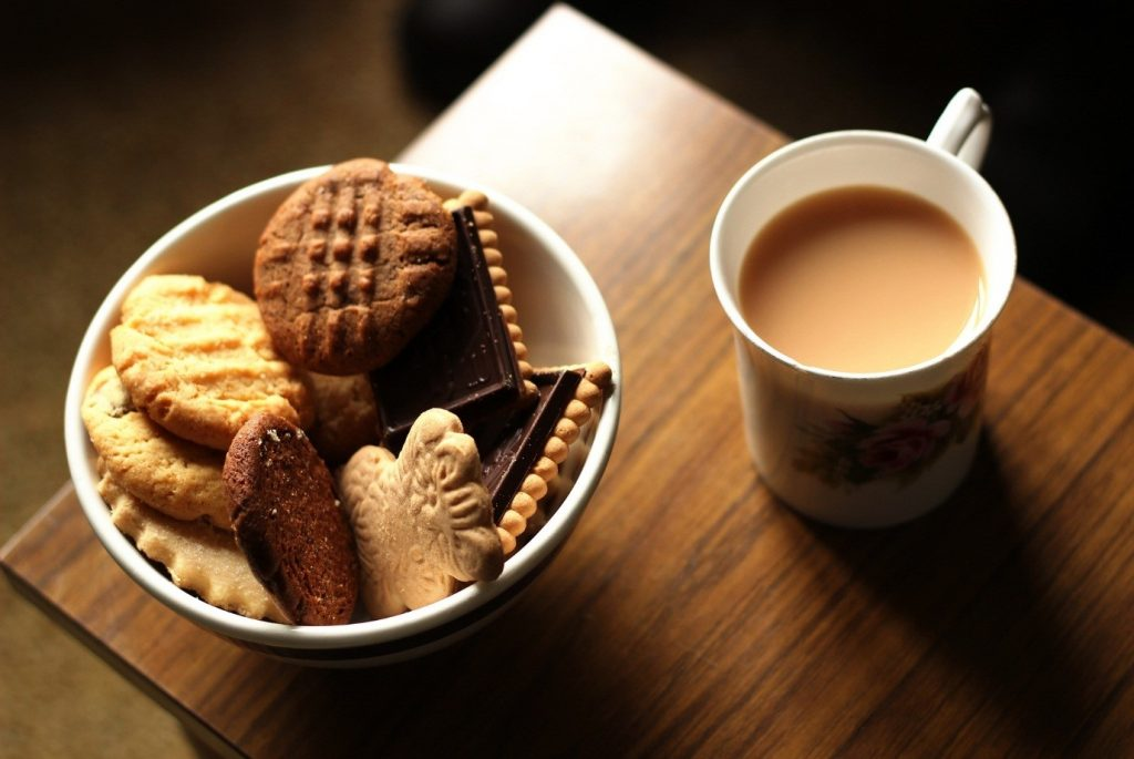 A cup of warm tea and a plate with a selection of biscuits celebrating British National Tea Day