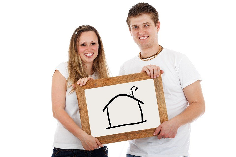 Happy couple holding picture of a new home